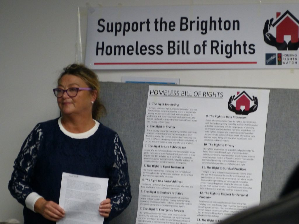 Picture of Nichole Brennan standing next to a poster containing the Homeless Bill of Rights